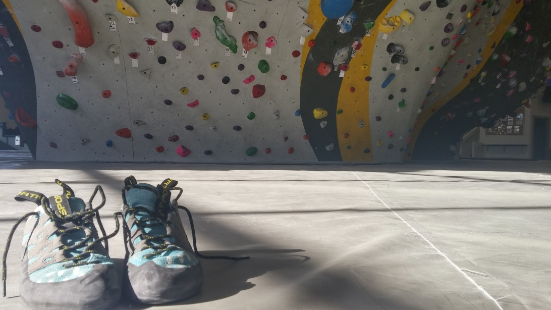 La Sportiva Tarantulace climbing shoes in front of a bouldering wall at Momentum in Lehi, Utah
