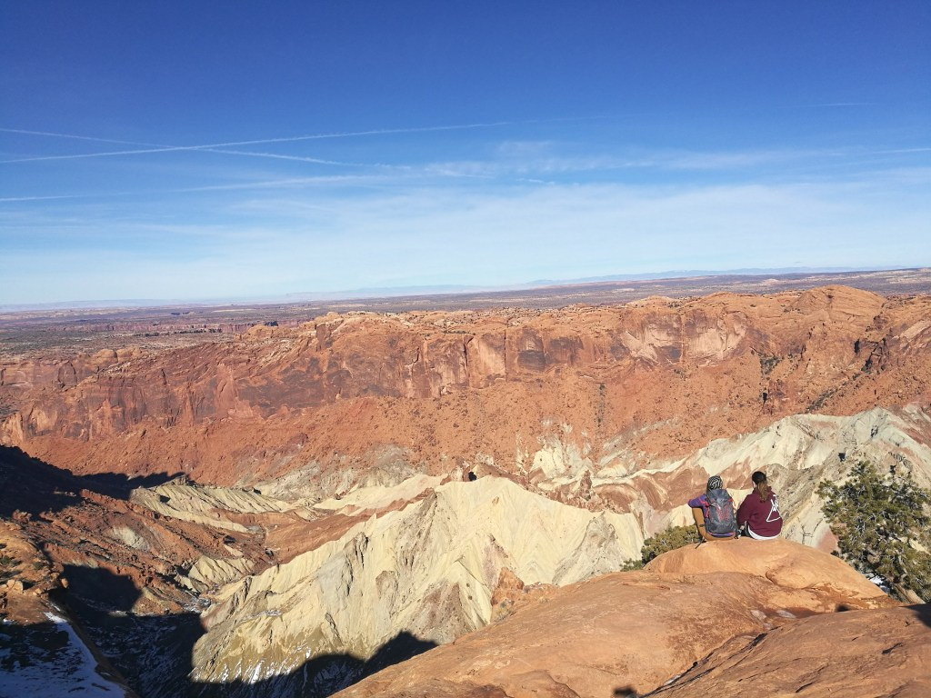 Anna and her friend sit at the overlook to Upheaval Dome in Canyonlands National Park.