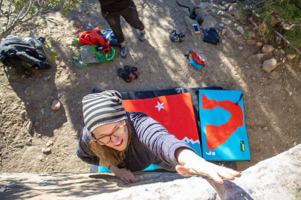 Anna bouldering in Joe's Valley with Organic Climbing crash pads below her.