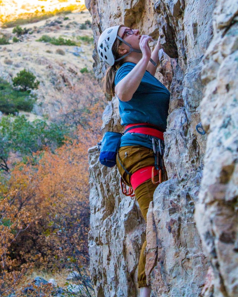 Anna lead climbing wearing an orange Petzl harness and a white Petzl helmet in Rock Canyon in Provo, Utah.